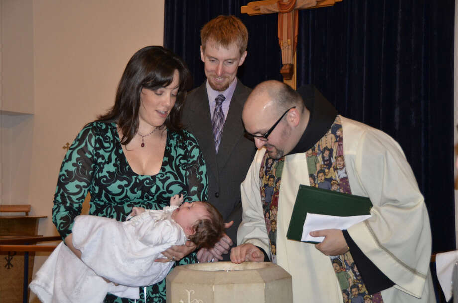 Father Jason Lody baptizes anew member of St. Anthony of Padua.  The church bills itself as inclusive. Photo: RNS Photo