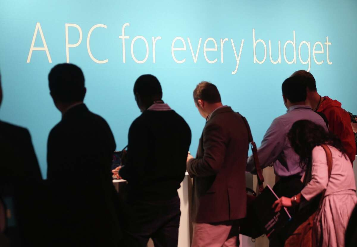 NEW YORK, NY - OCTOBER 25: People look at the Microsoft Windows 8 operating system at a press conference launch of the system on October 25, 2012 in New York City. Windows 8 will offer a touch interface in an effort to bridge the gap between tablets, smartphones and personal computers. Microsoft will also be selling a tablet called Surface to compete in the competitive tablet market. (Photo by Mario Tama/Getty Images)