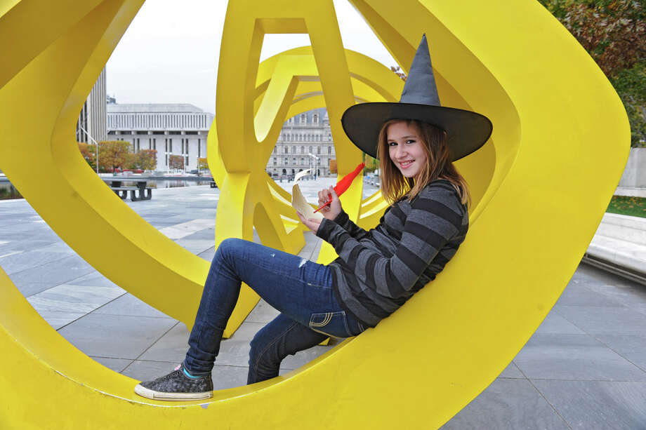 """Kylie Salerno, the grand prize winner of a Halloween storytelling contest sits on the George Sugarman statue titled """"Trio"""" at the Empire State Plaza Wednesday, Oct. 24, 2012 in Albany, N.Y. This is one of the statues Salerno wrote about. (Lori Van Buren / Times Union) Photo: Lori Van Buren"""