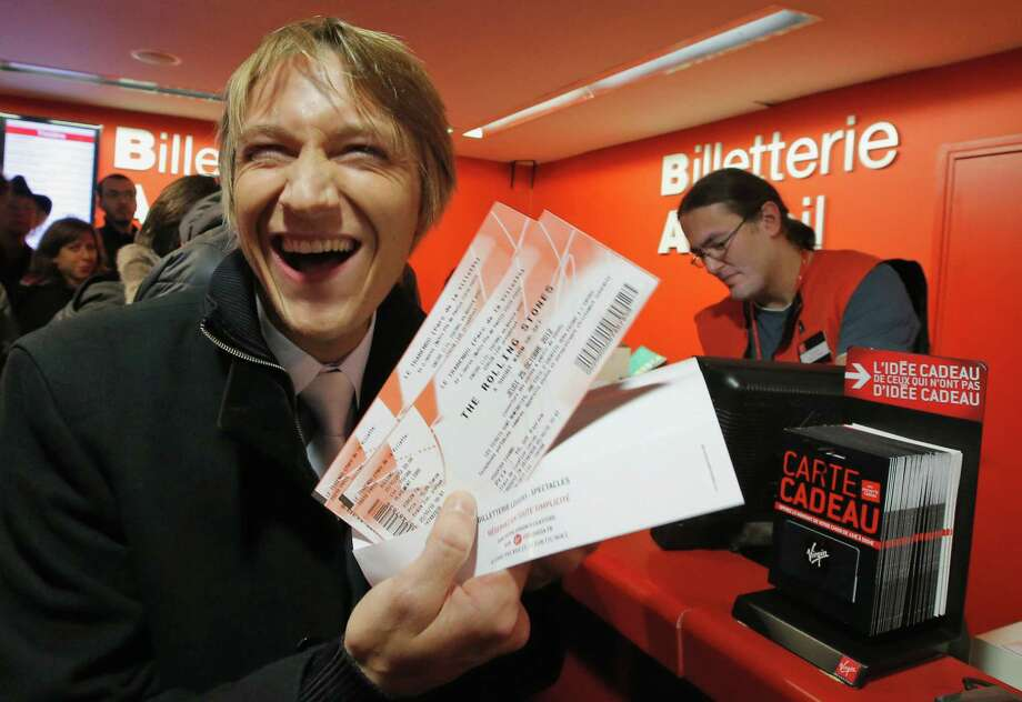 """Michael Evanno, 31, shows the tickets he bought for the Rolling Stones concert at Virgin Megastore in Paris, Thursday Oct. 25, 2012. The Rolling Stones announced a surprise """"warm-up gig"""" in Paris, and within an hour the Champs Elysees was swarming with fans hoping to get satisfaction with one of the 350 tickets for the Thursday night show. (AP Photo/Francois Mori) Photo: Francois Mori"""