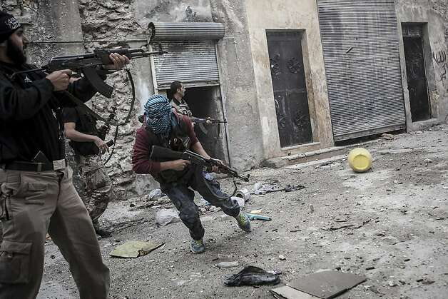 Rebel fighters retreat for cover during a clash with government forces in Aleppo, Syria. Photo: Narciso Contreras, Associated Press