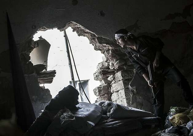 In this Wednesday, Oct. 24, 2012 photo, a Free Syrian Army fighter watches over an enemy position as rebel fighters belonging to the Liwa Al Tawhid group carry out a military operation at the Moaskar front line, one of the battlefields in the Karmal Jabl neighborhood, in Aleppo, Syria. (AP Photo/Narciso Contreras) Photo: Narciso Contreras, Associated Press