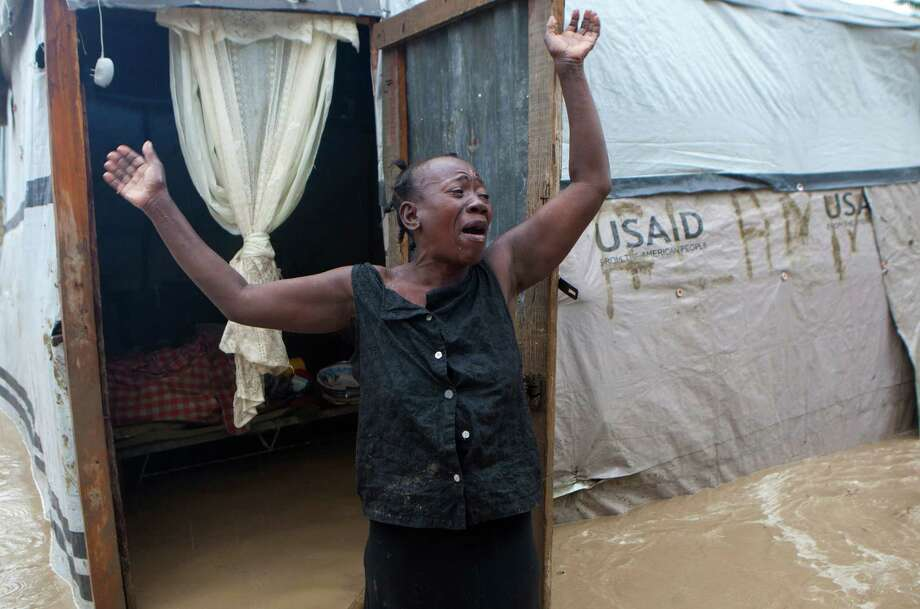 A woman cries in despair over the flooding of her house in Port-au-Prince, Haiti, in the wake of heavy rains spawned by Hurricane Sandy. The storm rumbled across Cuba on Thursday, heading toward the Bahamas. Photo: Dieu Nalio Chery, STR / AP