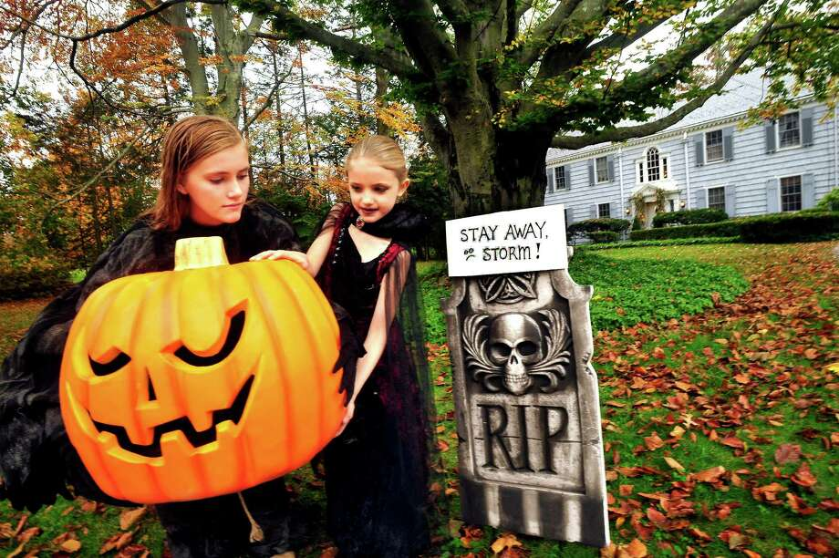 Sophie Rundhaug, 12, and her sister, Grace, 7, put Halloween decorations outside their Danbury home Thursday, Oct. 25, 2012. Photo: Michael Duffy