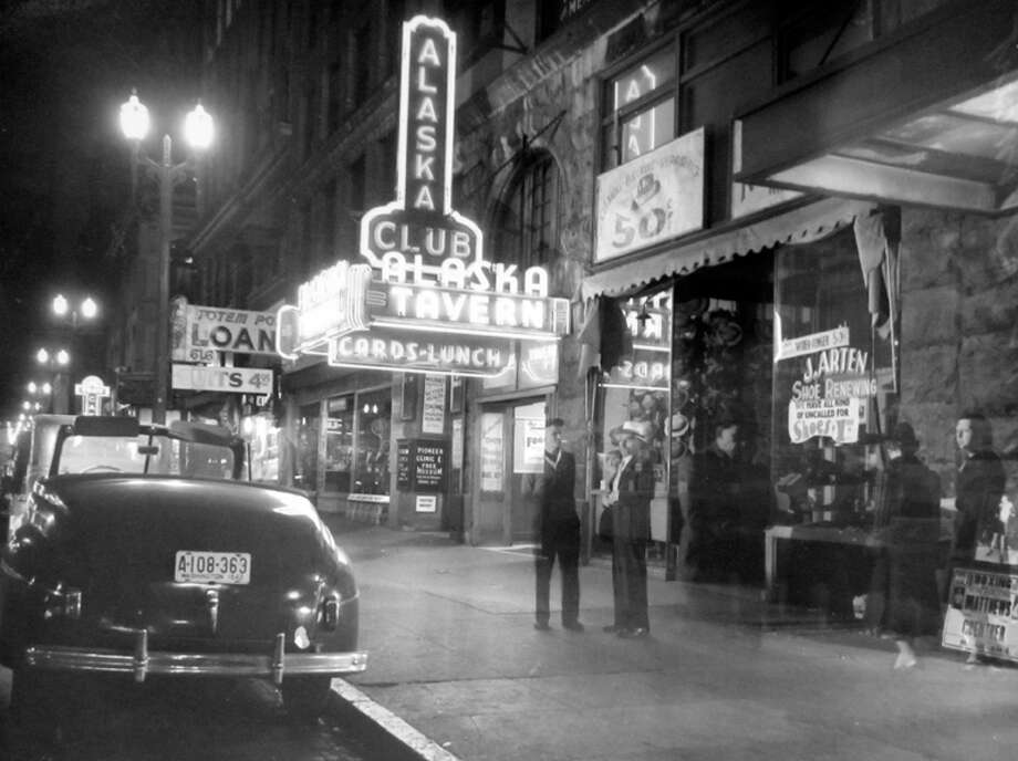 According to notes at MOHAI, this picture of the Alaska Club, 612 First Ave., was taken during a blackout night in August 1942. Not all club signs were dimmed. Photo: MOHAI, Seattle-Post-Intelligencer Collection