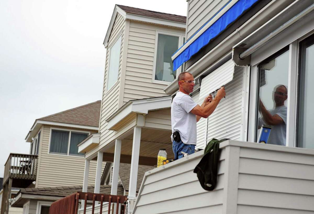 Mark Legenos installs hurricane shutters on a home on West Beach Drive in Stratford Thursday, Oct. 25, 2012. Legenos estimated the company he works for, Shade and Shutter Systems, Inc., saw a 30% increase in sales following Hurricane Irene.