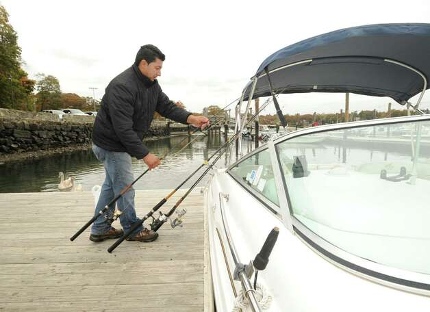 Juan Silva of Byram collects fishing gear from his motor boat after a day of fishing on Long Island Sound at the Byram docks, Thursday afternoon, Oct. 25, 2012.  Silva said he will wait to this weekend to decide what action to take with his vessel before the expected Hurricane Sandy hits the area on Monday or Tuesday. Photo: Bob Luckey / Greenwich Time