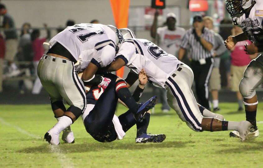 Hardin-Jefferson quarterback Jared Gieseke is tackled by a host of West Orange-Stark defenders durin