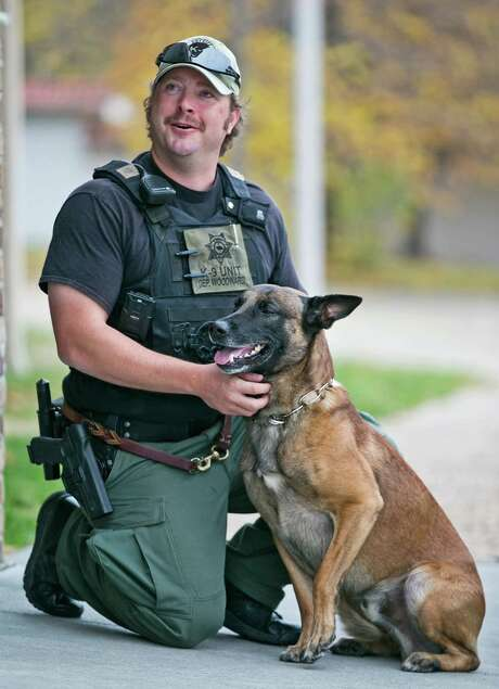 In this Oct. 22, 2012 photo, Douglas County Sheriff's Deputy Andy Woodward is shown with his K-9 partner,  Diezel, a Belgian Malinois, in Omaha, Neb. Woedward is being dropped by his home insurance company, who says the police dog he keeps at his home is a risk it is not willing to bear. And the head of the nation?s largest police union warns American Family Insurance Co. to prepare to be shunned by its 325,000 members.  (AP Photo/The Omaha World-Herald,Jeff Beiermann)  MAGS OUT TV OUT INTERNET OUT Photo: Jeff Beiermann, MBI / OMAHA WORLD-HERALD