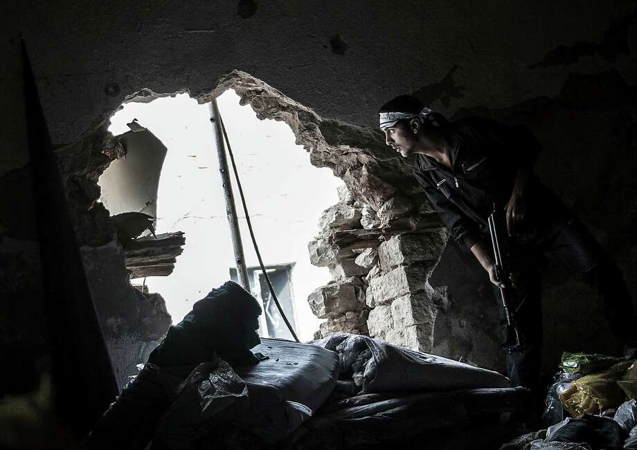 A Free Syrian Army fighter stares at an enemy position Thursday as rebel fighters carry out a military operation at the Moaskar front line in Aleppo, Syria. Photo: Narciso Contreras, STR / Narciso Contreras