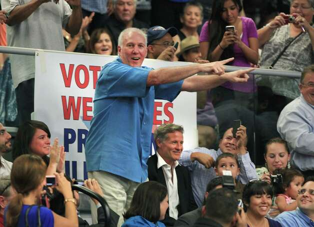 Spurs Coach Gregg Popovich tries to direct attention back to former President Bill Clinton at South San High School in San Antonio during a Democrat Rally.  Seated next to Popovich is Assistant Coach Brett Brown.  Thursday, Oct. 25, 2012. Photo: Bob Owen, San Antonio Express-News / San Antonio Express-News