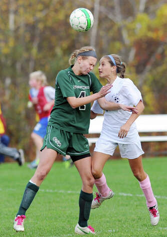 At left, Lexie Miller # 4 of Convent of the Sacred Heart heads the ball while being defended by Sam Kost # 2 of Rye Country Day School during the high school soccer match between Convent of the Sacred Heart and Rye Country Day School at Convent in Greenwich, Thursday afternoon, Oct. 25, 2012. Photo: Bob Luckey / Greenwich Time