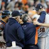 A trainer looks at Detroit Tigers starting pitcher Doug Fister after getting hit by a ball off the bat of San Francisco Giants' Gregor Blanco during the second inning of Game 2 of baseball's World Series Thursday, Oct. 25, 2012, in San Francisco. (AP Photo/David J. Phillip)