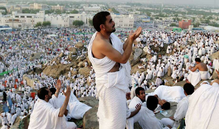 Muslim pilgrims pray on a rocky hill called the Mountain of Mercy on the Plain of Arafat near the holy city of Mecca, Saudi Arabia, Thursday, Oct. 25, 2012.  (AP Photo/Hassan Ammar) Photo: Hassan Ammar, Associated Press / AP