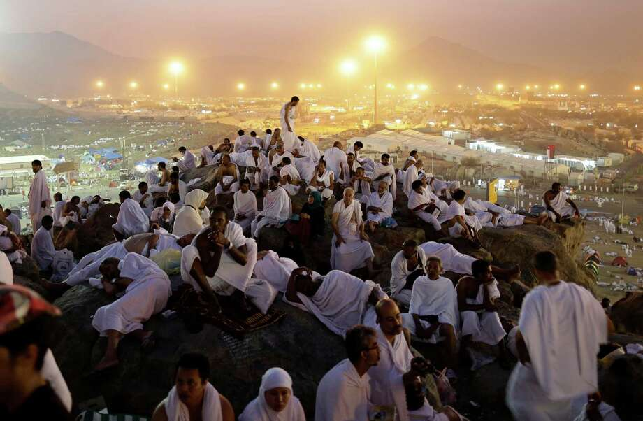 Muslim pilgrims pray on a rocky hill called the Mountain of Mercy, on the Plain of Arafat near the holy city of Mecca, Saudi Arabia, in the early hours of Thursday, Oct. 25, 2012.  (AP Photo/Hassan Ammar) Photo: Hassan Ammar, Associated Press / AP