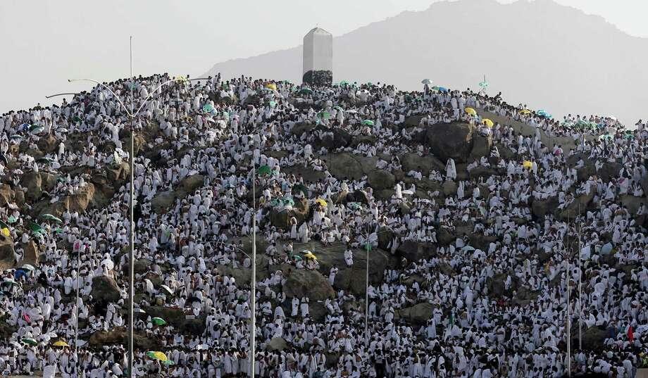 Muslim pilgrims pray on a rocky hill called the Mountain of Mercy on the Plain of Arafat near the holy city of Mecca, Saudi Arabia, Thursday, Oct. 25, 2012.  (AP Photo/Hassan Ammar) Photo: Hassan Ammar, Associated Press / AP