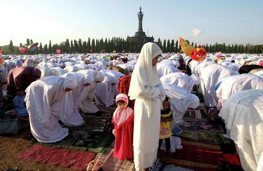 Indonesian children wear Muslim outfit as they stand between prayers at a field during Eid al-Adha celebration, Friday morning, Oct. 26, 2012 in Denpasar, Bali, Indonesia. Eid al-Adha, the celebration of sacrifice, is the second most important festival in the Muslim calendar, marking the end of the Hajj, the annual pilgrimage to Mecca. (AP Photo/Firdia Lisnawati) Photo: Firdia Lisnawati, Associated Press / AP