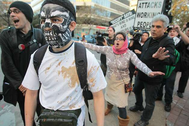 Demonstrators ask a masked man to leave Oakland's Frank Ogawa Plaza after he made white supremacist comments during the first anniversary of the dismantling of the group's camp. Photo: Mathew Sumner, Special To The Chronicle / SF