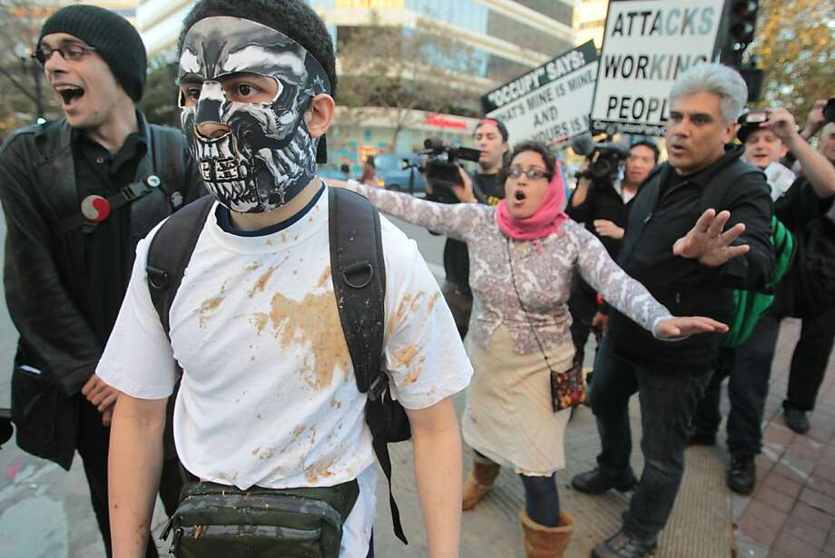 Demonstrators ask a masked man to leave Oakland's Frank Ogawa Plaza after he made white supremacist comments during the first anniversary of the dismantling of the group's camp. Photo: Mathew Sumner, Special To The Chronicle