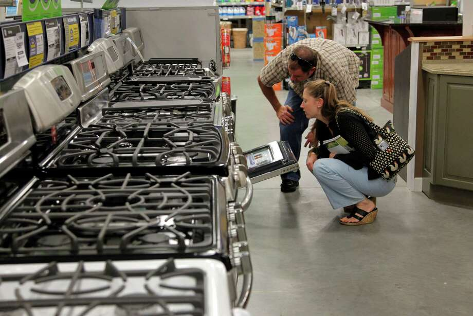 In this Monday, Sept. 10, 2012 photo Brian Gibson, top right, and his wife Elizabeth Gibson, below right, both of Framingham, Mass., examine stoves at a Lowe's store location in Framingham.  U.S. companies remained cautious in September and held back on orders for long-lasting manufactured goods that signal investment plans. (AP Photo/Steven Senne) Photo: Steven Senne