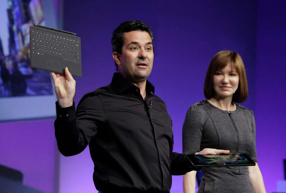 Mike Angiulo, corporate vice president of the Planning and PC Ecosystem team at Microsoft, shows the company's Surface tablet computer, and detachable keyboard, at the launch of Microsoft Windows 8, in New York,  Thursday, Oct. 25, 2012. Windows 8 is the most dramatic overhaul of the personal computer market's dominant operating system in 17 years. He is accompanied by Microsoft Vice President Julie Larson-Green. (AP Photo/Richard Drew) Photo: Richard Drew