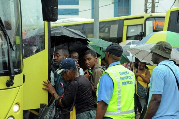 Commuters board a bus as rain brought by the outer bands of Tropical Storm Sandy fall in Kingston, Jamaica, Tuesday, Oct. 23, 2012. The U.S. National Hurricane Center in Miami said Sandy was expected to become a hurricane as it nears Jamaica on Wednesday. (AP Photo/Collin Reid) Photo: Collin Reid