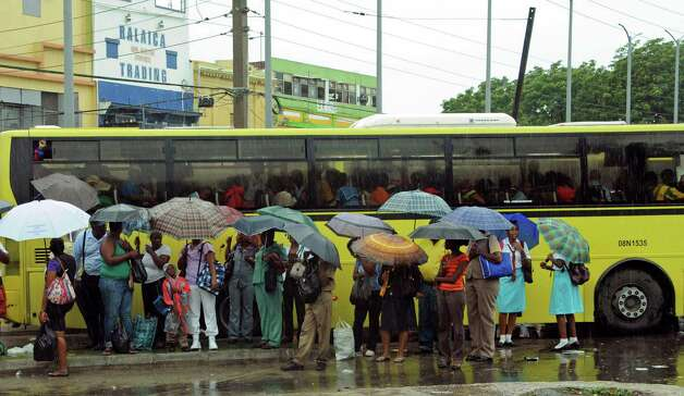 Commuters wait at a bus stop as rain brought by the outer bands of Tropical Storm Sandy falls in Kingston, Jamaica, Tuesday, Oct. 23, 2012. The U.S. National Hurricane Center in Miami said Sandy was expected to become a hurricane as it nears Jamaica on Wednesday. (AP Photo/Collin Reid) Photo: Collin Reid