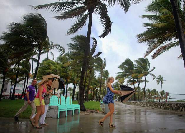 MIAMI BEACH, FL - OCTOBER 25: (L-R) William Rath, Julie Rath, Laura Rath and Weera Rath, on vacation from the Netherlands, walk to the beach as they are buffeted by high winds of the outer bands of Hurricane Sandy on October 25, 2012 in Miami Beach, Florida. After passing over Jamaica Hurricane Sandy is expected to hit eastern Cuba and head into the Bahamas today and tomorrow. There is a tropical storm warning in place for coastal Miami-Dade, Broward, and Palm Beach Counties and the Atlantic waters off southeast Florida. (Photo by Joe Raedle/Getty Images) Photo: Joe Raedle