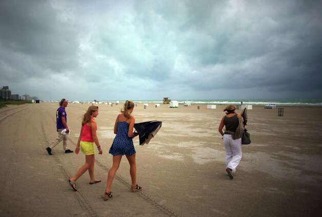 MIAMI BEACH, FL - OCTOBER 25: (L-R) William Rath, Julie Rath, Weera Rath and Laura Rath, on vacation from the Netherlands, walk on the beach as they are buffeted by high winds of the outer bands of Hurricane Sandy on October 25, 2012 in Miami Beach, Florida. After passing over Jamaica Hurricane Sandy is expected to hit eastern Cuba and head into the Bahamas today and tomorrow. There is a tropical storm warning in place for coastal Miami-Dade, Broward, and Palm Beach Counties and the Atlantic waters off southeast Florida. (Photo by Joe Raedle/Getty Images) Photo: Joe Raedle