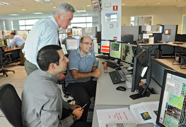 Meteorologist In Charge Ray O'Keefe, standing, confers with meteorologists Joe Villani, left, and Tom Wasula as they work on tracking Hurricane Sandy at the National Weather Service on Fuller Rd. on Thursday, Oct. 25, 2012 in Albany, N.Y.  (Lori Van Buren / Times Union) Photo: Lori Van Buren