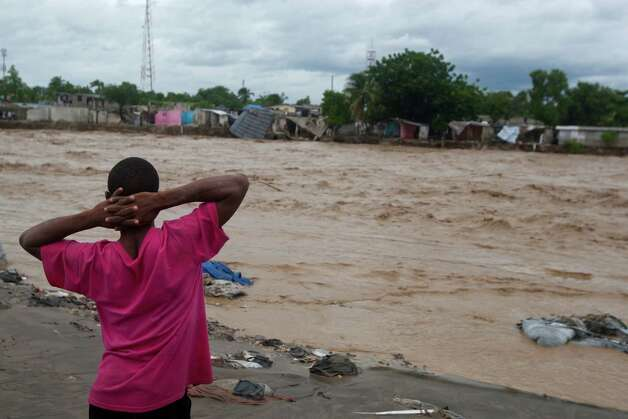 A man watches a river affected by heavy rains brought by Hurricane Sandy in Port-au-Prince, Haiti, Thursday, Oct. 25,  2012. Sandy was blamed for the death of an elderly man in Jamaica who was crushed by a boulder. Another man and two women died while trying to cross storm-swollen rivers in southwestern Haiti. (AP Photo/Dieu Nalio Chery) Photo: Dieu Nalio Chery