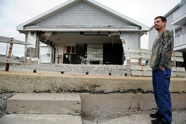 John Steinbach who lives on Point Beach Drive in Milford stands in front of the shell of a neighbor's beachfront home Thursday, Oct. 25, 2012.  The house was destroyed during Hurricane Irene. Photo: Autumn Driscoll