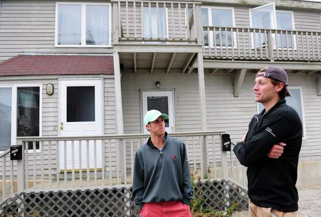Brendan O'Brien, 21, left, and Scott Rainaud, 21, both students at Fairfield University, stand outside the house they rent on Fairfield Beach Road in Fairfield Thursday, Oct. 25, 2012. Photo: Autumn Driscoll