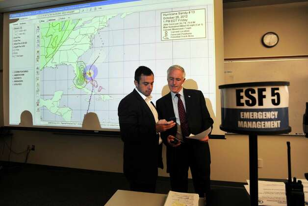 Peter Finch and his dad, Mayor Bill Finch go over the social media aspect of keeping people informed during an emergency. The Mayorand City public safety officials discuss storm preparedness for hurricane Sandy in a meeting at the Emergency Operations Center, 581 North Washington Ave., in Bridgeport, Conn. on Thursday, Oct. 25, 2012. Photo: Cathy Zuraw