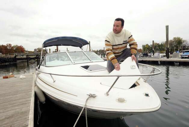 Alex Cepeda of Port Chester, N.Y., secures the front hatch on the motor boat of friend Juan Silva after a day of fishing on Long Island Sound, at the Byram docks, Thursday afternoon, Oct. 25, 2012. Hurricane Sandy is expected to hit the area on Monday or Tuesday and mariners are making preparations to secure their vessels. Photo: Bob Luckey / Greenwich Time