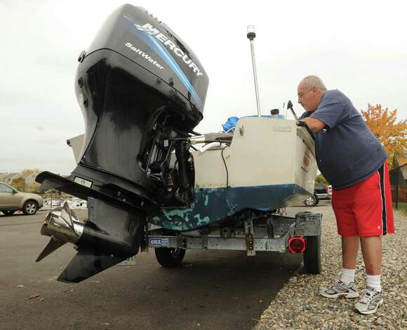 Marco Junquira of Rizzi Marine Sales and Service of Cos Cob disconnects a pair of batteries from an outboard motor on a power boat at the Cos Cob docks, Thursday afternoon, Oct. 25, 2012.  Hurricane Sandy is expected to hit the area on Monday or Tuesday and mariners are making preparations to secure their vessels. Photo: Bob Luckey / Greenwich Time