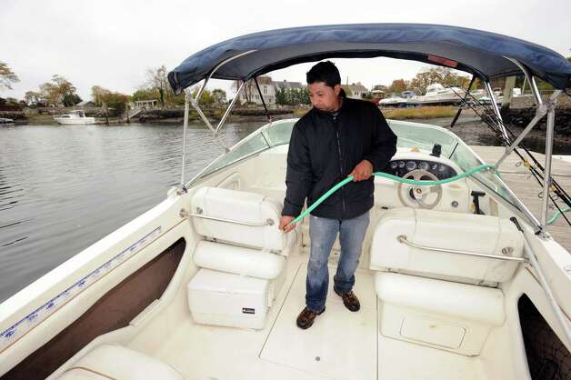 Juan Silva of Byram hoses off the interior of his motor boat after a day of fishing on Long Island Sound at the Byram docks, Thursday afternoon, Oct. 25, 2012.  Silva said he will wait to this weekend to decide what action to take with his vessel before the expected Hurricane Sandy hits the area on Monday or Tuesday. Photo: Bob Luckey / Greenwich Time