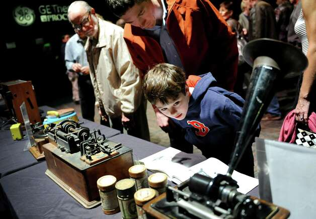Kiernan Stone, 9, of Charleton, right, and his father, Kevin, look at sound equipment invented by Thomas Edison on Thursday, Oct. 25, 2012, at the GE Theatre at Proctors in Schenectady, N.Y. From left center, are an 1890 battery-operated phonograph, wax cylinders from the early 1900s and a standard phonograph circa 1905. (Cindy Schultz / Times Union) Photo: Cindy Schultz / 00019840A