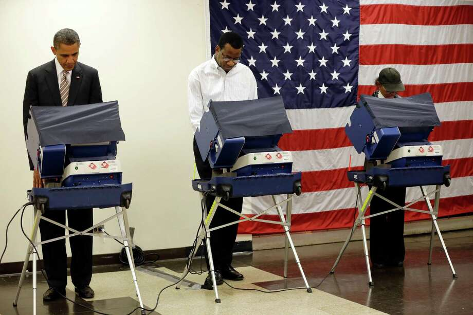 President Barack Obama, left, casts his vote during early voting in the 2012 election Thursday, Oct. 25, 2012, in Chicago, at the Martin Luther King Community Center. (AP Photo/Pablo Martinez Monsivais) Photo: Pablo Martinez Monsivais