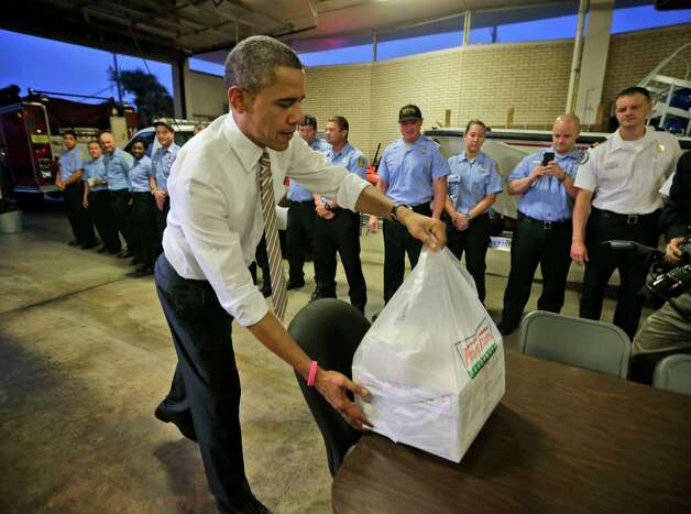 President Barack Obama delivers boxes of Krispy Kreme doughnuts, that he purchased nearby, to firefighters at Fire Station No. 14., during an unannounced visit, Thursday, Oct. 25, 2012, in Tampa, Fla. (AP Photo/Pablo Martinez Monsivais) Photo: Pablo Martinez Monsivais