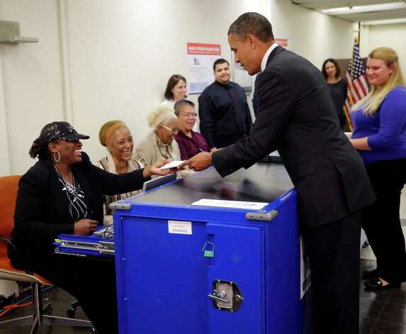 President Barack Obama, right, turns in his ballot receipt to election official Marie Holmes, left, as he prepares to cast his vote, during early voting, in the 2012 election at the Martin Luther King Community Center, Thursday, Oct. 25, 2012, in Chicago. (AP Photo/Pablo Martinez Monsivais) Photo: Pablo Martinez Monsivais