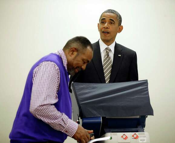 President Barack Obama, right, reacts to election official Eli Selph's cell ringing as he casts his vote, during early voting, in the 2012 election at the Martin Luther King Community Center, Thursday, Oct. 25, 2012, in Chicago. (AP Photo/Pablo Martinez Monsivais) Photo: Pablo Martinez Monsivais