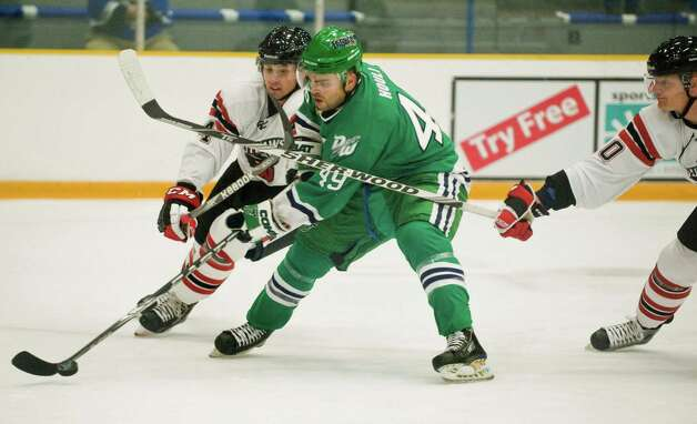 Williamsport Outlaws Dan McNeill, left, checks Danbury Whalers Adam Houli during a game played at the Danbury Arena. Thursday, Oct. 25, 2012 Photo: Scott Mullin