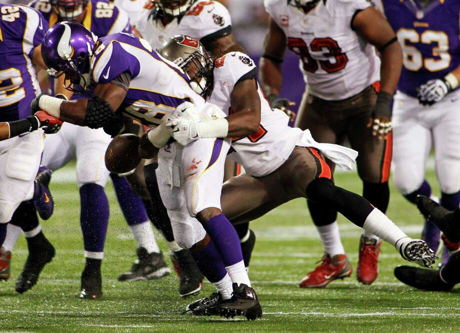 Minnesota Vikings running back Adrian Peterson, left, fumbles the ball as he is tackled by Tampa Bay Buccaneers strong safety Mark Barron during the first half of an NFL football game Thursday, Oct. 25, 2012, in Minneapolis. Th Buccaneers recovered the ball. (AP Photo/Andy King) Photo: Andy King