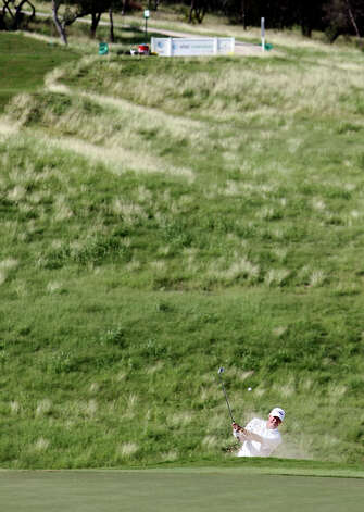 Pro golfer Russ Cochran hits his ball out of a green-side bunker on No. 16 on the last day of the AT&T Champion pro-am rounds at the TPC San Antonio, Canyons Course on Thursday, Oct. 25, 2012. The par three, No. 16 is expected to be a tough hole for the players this weekend. Photo: Kin Man Hui, Express-News / © 2012 San Antonio Express-News