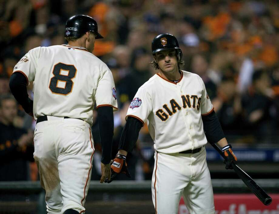 The San Francisco Giants' Hunter Pence (8) returns to the dugout after scoring and is greeted by Ryan Theriot in the eighth inning in Game 2 of the 2012 World Series at AT&T Park on Thursday, October 25, 2012, in San Francisco, California. The Giants won, 2-0, to take a 2-0 series lead. (Paul Kitagaki Jr./Sacramento Bee/MCT) Photo: Paul Kitagaki Jr., McClatchy-Tribune News Service / ARCHIVE