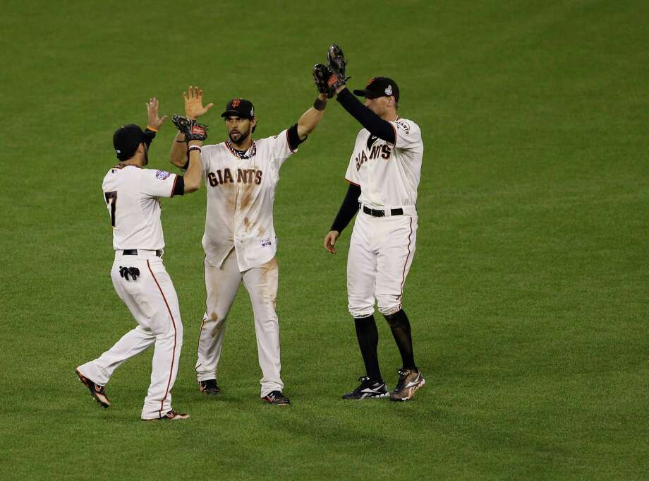 San Francisco Giants' Gregor Blanco, left, Angel Pagan, middle, and Hunter Pence celebrates after the Giants defeated the Detroit Tigers, 2-0, in Game 2 of baseball's World Series Thursday, Oct. 25, 2012, in San Francisco. (AP Photo/Jeff Chiu) Photo: Jeff Chiu, Associated Press / AP