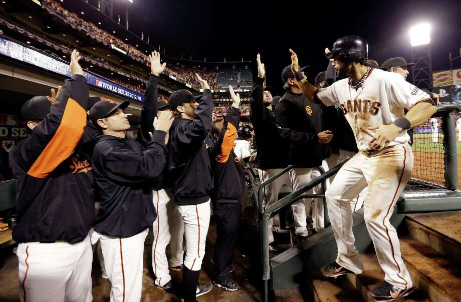 San Francisco Giants' Marco Scutaro is congratulated in the dugout after scoring on a sacrifice fly by Hunter Pence during the eighth inning of Game 2 of baseball's World Series against the Detroit Tigers Thursday, Oct. 25, 2012, in San Francisco. (AP Photo/David J. Phillip) Photo: David J. Phillip, Associated Press / AP