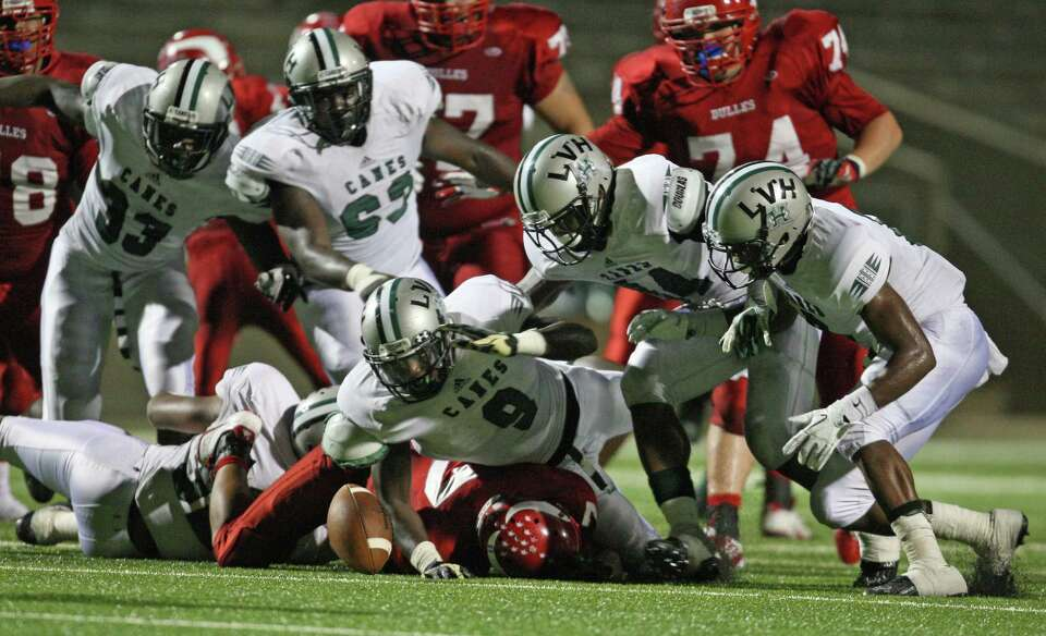 Hightowerlinebacker Matthew Adams (9) and as wall of Hurricane defenders try to recover a fumble by