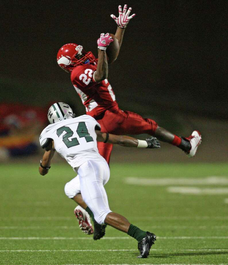 Dulles wide receiver Raevon Felton (22) makes a leaping reception as Hightower defensive back Joshua Cook defends during the first half of a high school football game, Thursday, October 25, 2012 at Mercer Stadium in Sugar Land TX. Photo: Eric Christian Smith, For The Chronicle